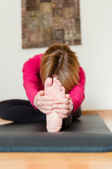 Middle aged woman stretching on a yoga mat at home. Yoga concept