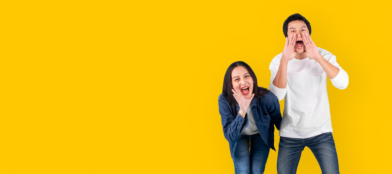 Asian couple man and woman shout and announce with loud over yellow background with copy space