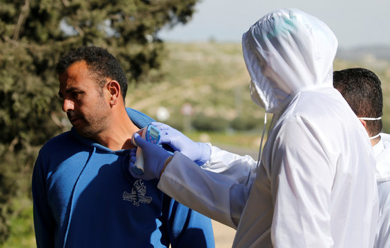 A member of medical staff checks the body temperature of a Palestinian worker returning from Israel, outside the Israeli-controlled Tarqumiya checkpoint in the Israeli-occupied West Bank