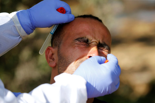 A member of medical staff swabs the nose of a Palestinian worker outside the Israeli-controlled Tarqumiya checkpoint in the Israeli-occupied West Bank