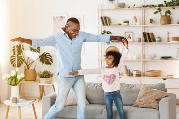 Stay at home leisure. Senior African American man dancing with his granddaughter indoors
