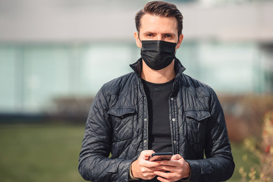 Man wearing a mask on a background of a modern building,