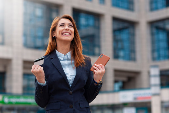 Happy business woman holding credit card and phone outdoor