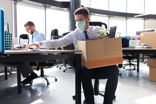 Dismissal employee in an epidemic coronavirus. Sad dismissed worker are taking his office supplies with him from office.