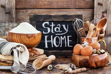 Baking ingredients and board with social notice stay at home