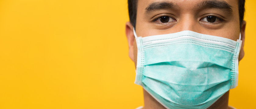 Close up young asian man wearing protection face mask against coronavirus on yellow background.