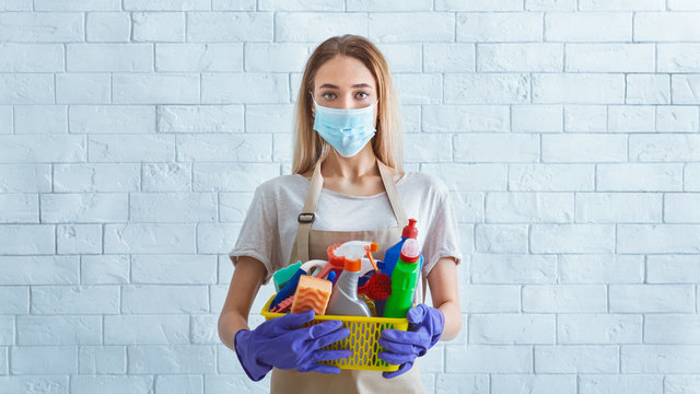 Girl in protective mask with cleaning supplies