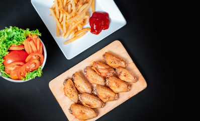 fast food , french fries and fried chicken , with green salad, tomatoes on dark table, top view