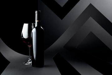 Bottle and glass of red wine on a dark background.