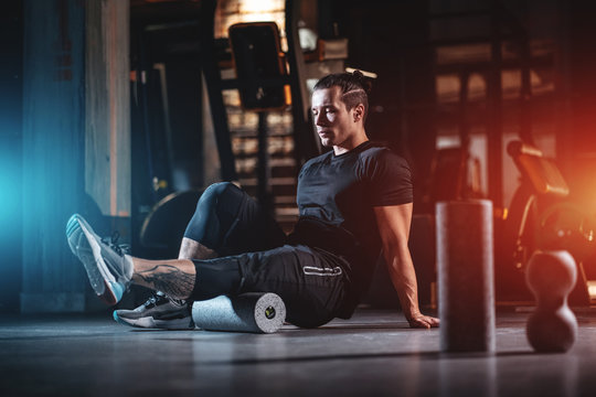 young man has crossfit workout with roller and weight in gym