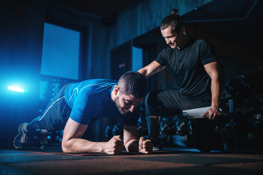 young man has workout with personal trainer in modern gym