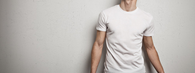 man in blank t-shirt, white grunge wall background. Wide screen. Wide screen panoramic
