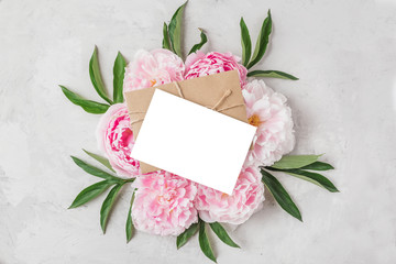 Blank greeting card with pink peony flowers on concrete background. Wedding invitation. Flat lay. Mock up