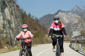 Mother and daughter biking and wearing medical mask