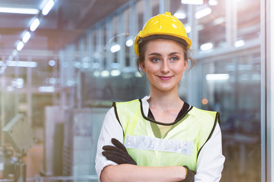 Portrait of manual woman worker is standing with confident with blue working suite green reflect for safty dress and helmet in front the glass wall of high technology clean industry factory.