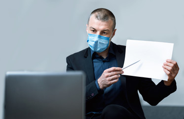 Businessman In Mask Communicating With Colleagues Via Video Call Indoor