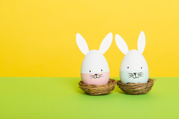 Two easter eggs with bunny faces in nest on a green and yellow background with space for copy