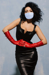 Beautiful adult woman wearing in protection mask black spandex dress and long red leather gloves