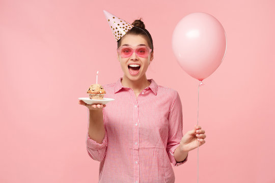 Excited birhday girl celebrating, holding air balloon and cake,  isolated on pastel pink studio background