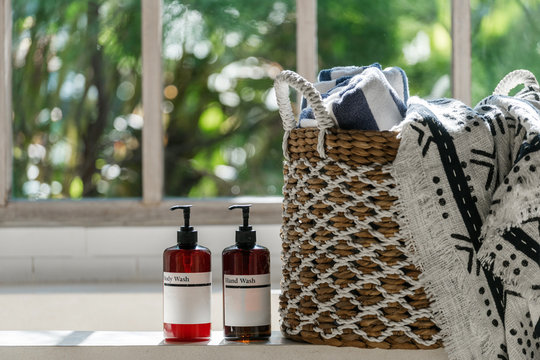 Large towels in wicker basket standing near two bottle of body care cosmetic products on bathtub top