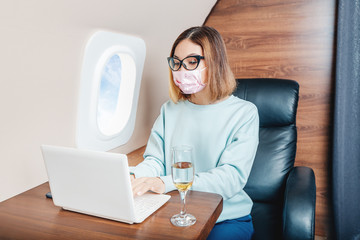 Asian girl in medical mask remote working on a laptop during flight on the airplane. Concept of a coronavirus covid19 and pneumonia pandemic Fototapete