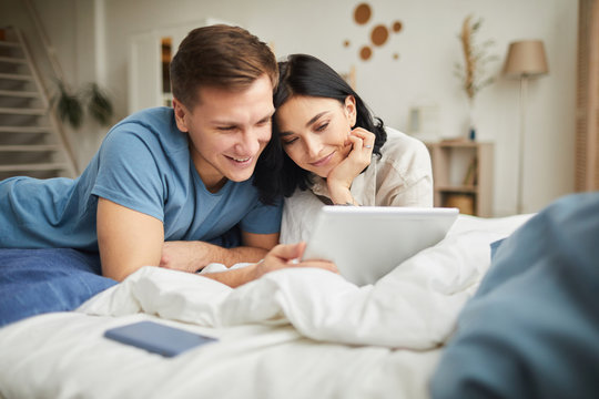 Portrait of young happy couple using digital tablet while lying on bed at home and ordering food online or watching movie, copy space