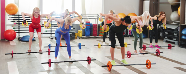 Women group workout with trainer in gym. Body pump training with barbells Wall mural