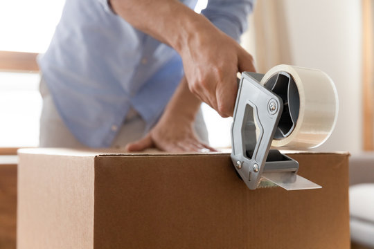Close up young man using adhesive scotch, packing carton parcel box at home. Male removal service worker holding tape dispenser, preparing family belongings to moving day, relocation concept.