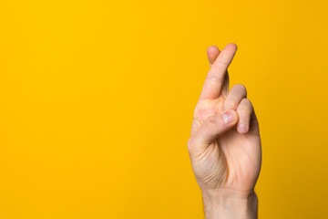fingers crossed hope sign. close up man hand symbolising faith against yellow background