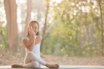 calmness and relax, female happiness.Horizontal, blurred background. little asian girl meditates while practicing yoga. freedom concept. calmness and relax, woman happiness. toned picture healthy life
