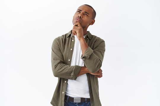 Hmmm interesting. Portrait of thoughtful handsome, smart african american man thinking, making choice, squinting and looking up, pondering decision, standing white background