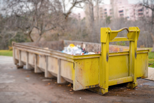 Yellow dumpster seen on a street near a park. The dumpster is filled to the top with plastic trash bags and other debris. Selective focus.
