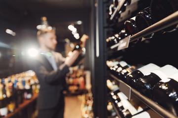 Bartender sommelier takes bottle of red wine from counter of restaurant drinks store