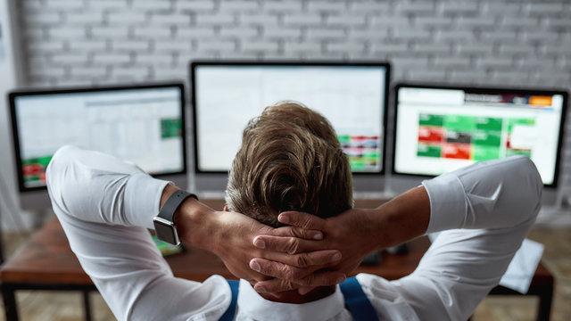 An awesome financial state of mind. Rear view of middle-aged trader sitting back in front of pc and analyzing stock market chart, while working in the office.