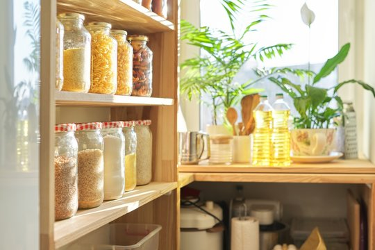Kitchen utensils, sunflower oil on wooden table in pantry, food storage at home