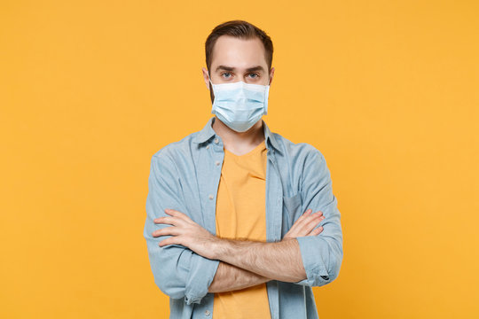 Young man in sterile face mask posing isolated on yellow background studio portrait. Epidemic pandemic rapidly spreading coronavirus 2019-ncov sars covid-19 flu virus concept. Holding hands folded.