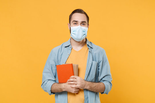Young man in sterile face mask posing isolated on yellow wall background studio portrait. Epidemic pandemic rapidly spreading coronavirus 2019-ncov sars covid-19 flu virus concept. Hold in hand books.