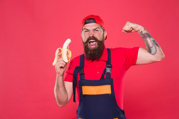 Fresh vitamins. Tasty food. Bite banana. Hungry hipster. Favorite snack. Lunch time. Bearded man in uniform and cap eating banana. Worker builder mechanic eat banana. Fresh fruit. Living healthy life