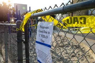 Playground closed due to COVID-19 sign with notice on chain link fence