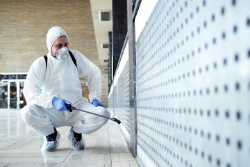 Shot of male person in white chemical protection suit doing disinfection of public areas to stop spreading highly contagious corona virus. Stop coronavirus or COVID-19. Fotobehang
