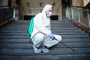 Shot of male person in white chemical protection suit disinfecting public corridors and steps to stop spreading highly contagious corona virus. Stop coronavirus or COVID-19.