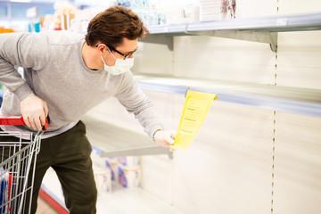 Mann vor einem leeren Regal in einer Drogerie, Toilettenpapier ist ausverkauft