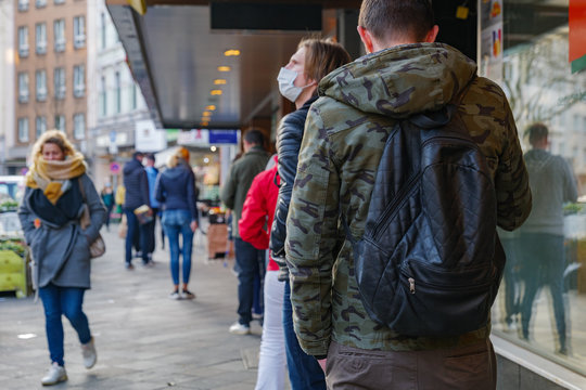 Selected focus, European people queue and wait on sidewalk outside in front of supermarket during quarantine for COVID-19 virus in Düsseldorf, Germany.