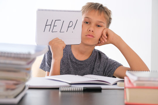 Upset tired preteen child sitting at the table, doing his homework among pile of books. Word Help is written on open notebook. Learning difficulties, school, education concept