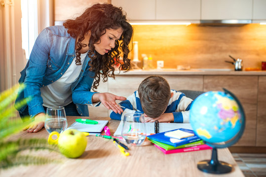 Mother Becoming Frustrated With Son Whilst Doing Homework. Mom makes the best teacher ever. Mother scolds a child for poor schooling and homework at home