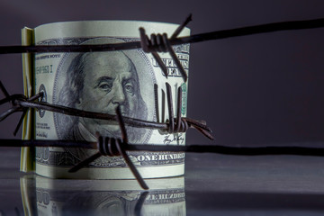 Economic warfare, sanctions and embargo busting concept. Close up US Dollar bills wrapped in barbed...