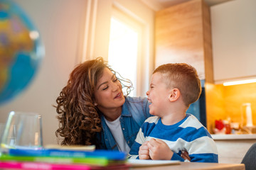 Kind mother helping her son doing homework in kitchen. Mother Helping Son With Homework At Table. Children's creativity. Portrait of smiling mother helping son with homework in kitchen at home