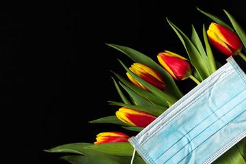 Coronavirus quarantine during Easter holidays. spring tulip flowers with face medical mask on black background