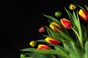 Easter background with Easter eggs and spring tulip flowers on black background. flat lay. top view