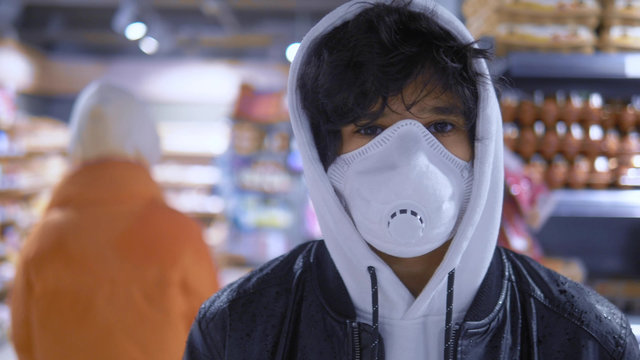 Portrait. brunette guy in a medical mask in a store. pandemic